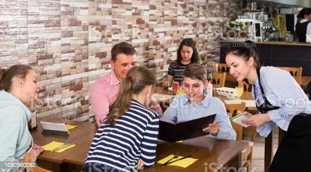 Happy parents with children are giving order to cheerful waitress