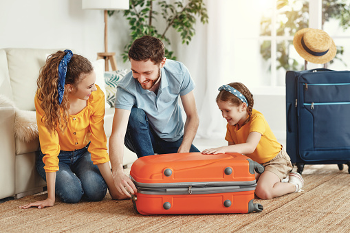 Smiling couple with charming little girl sitting on suitcase in living room   ready for summer trip