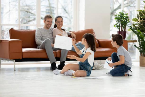 Happy parents with kids in living room enjoy leisure activities picture id1177916020?b=1&k=6&m=1177916020&s=612x612&w=0&h=xekjlgaz8frqga2iisibhazmolyxqnd blsks4knli4=