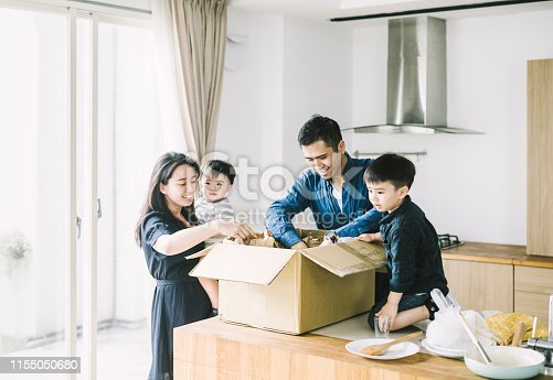 istock Happy parents with sons unpacking cardboard box 1155050680