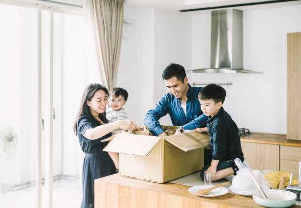 Happy parents with sons unpacking cardboard box stock photo