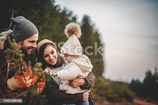 Happy parents with their daughter picking out a Christmas tree