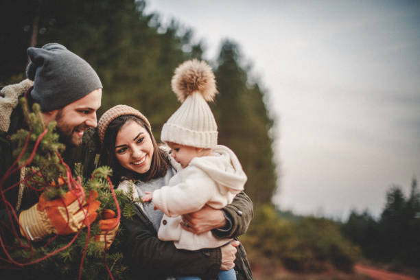 happy parents with their daughter picking out a christmas tree - family christmas imagens e fotografias de stock