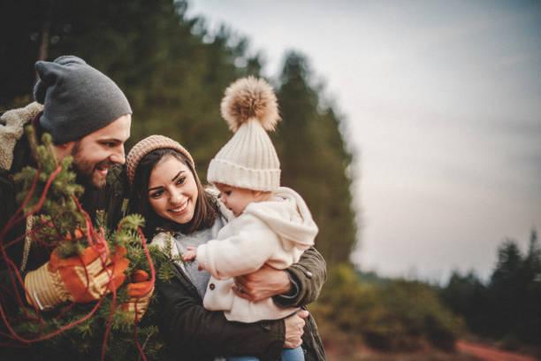 gelukkige ouders met hun dochter plukken uit een kerstboom - christmas family stockfoto's en -beelden