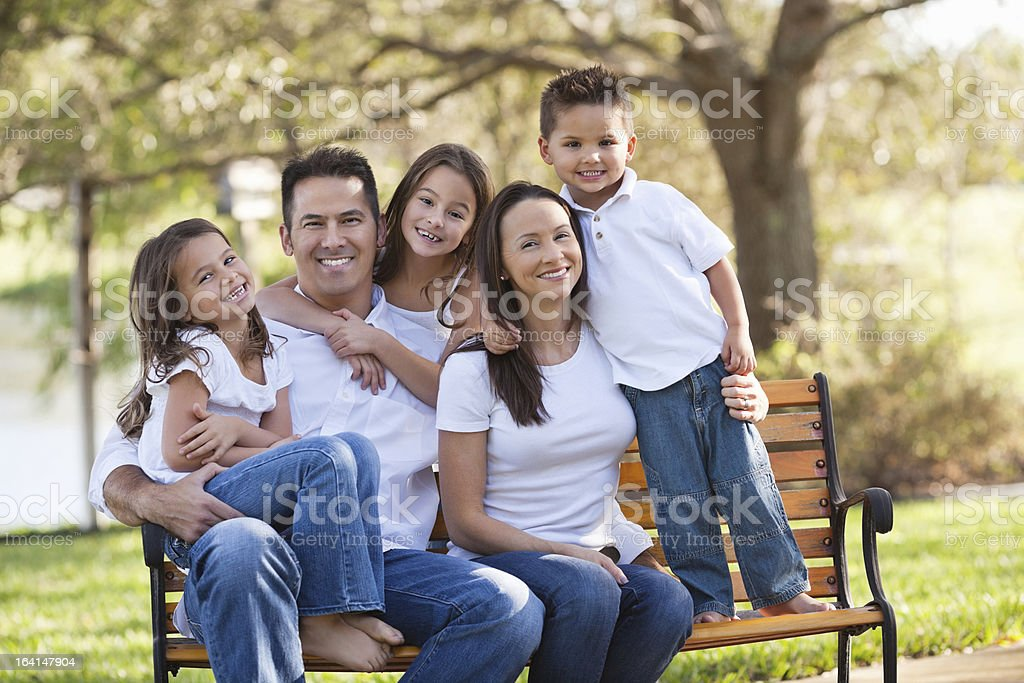 Happy Parents With Three Children At Park stock photo
