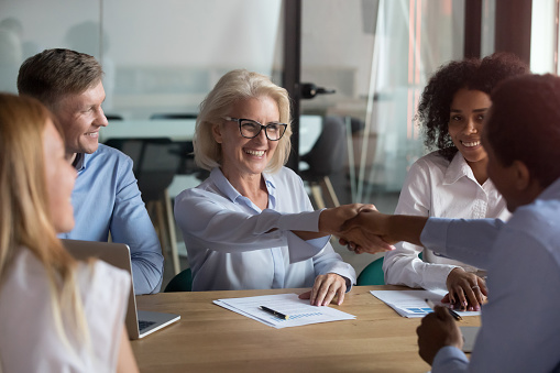 532257236 istock photo Happy partners shaking hands finish meeting successfully 1127397384