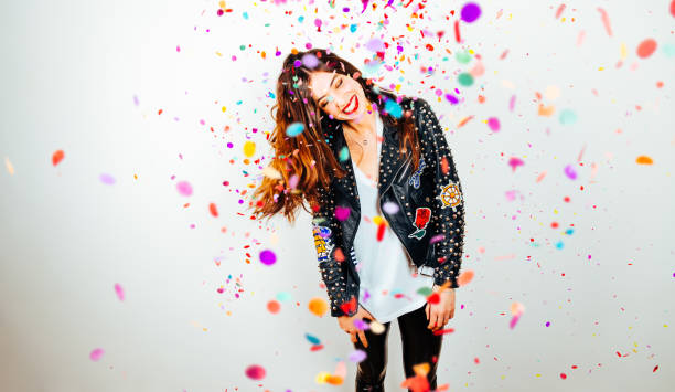 Happy party woman with confetti Happy young and beatiful woman with fashion leather jacket enjoying the party with confetti carnival celebration event stock pictures, royalty-free photos & images