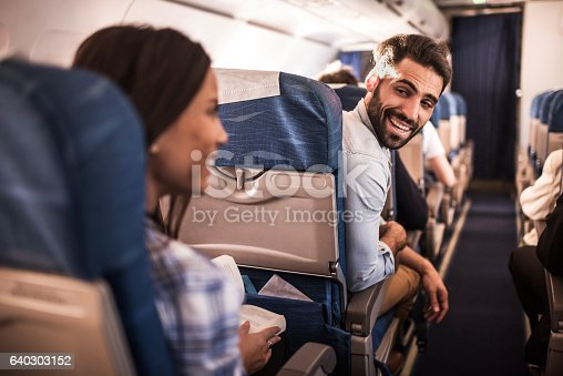 Happy man talking to young woman in the airplane.