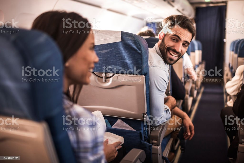 Happy passengers traveling by airplane and talking to each other. stock photo