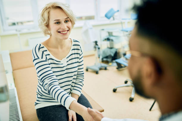 Happy patient visiting gynecologist Cheerful young woman thanking gynecologist and shaking his hand after consultation in clinic gynecological examination stock pictures, royalty-free photos & images