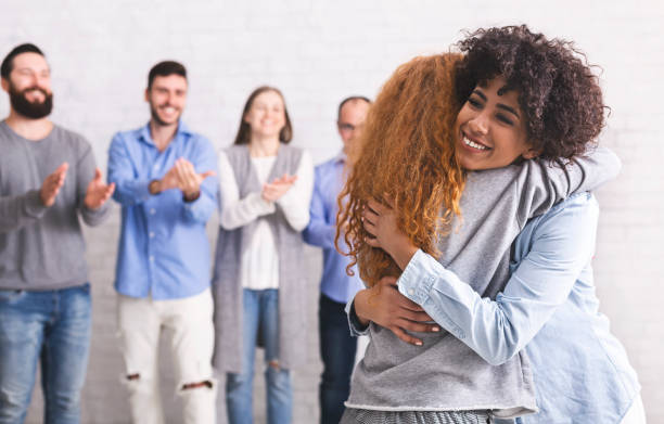 Happy patients embracing during support group session Group therapy meeting. Happy patients embracing during support session, free space drug rehab stock pictures, royalty-free photos & images