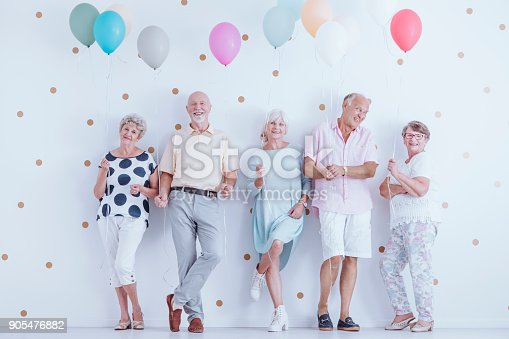 istock Happy pensioners holding balloons 905476882