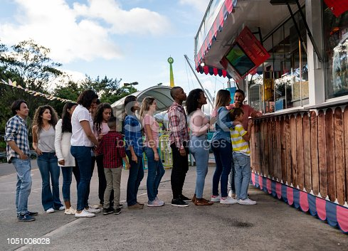Happy group of people buying food at an amusement park - lifestyle concepts