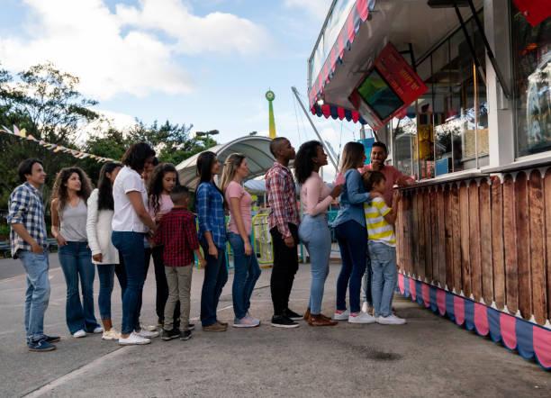Happy people buying food at an amusement park picture id1051006028?b=1&k=6&m=1051006028&s=612x612&w=0&h=nszntuuqzkoaf tszu0brwmbvn xi4ol9hu7jukszkk=