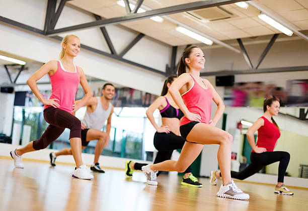 happy people doing lunge exercise in gym - aerobics stock photos and pictures