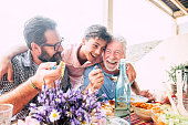 istock Happy people family concept laugh and have fun together with three different generations ages : grandfather father and young teenager son all together eating at lunch 1149200620