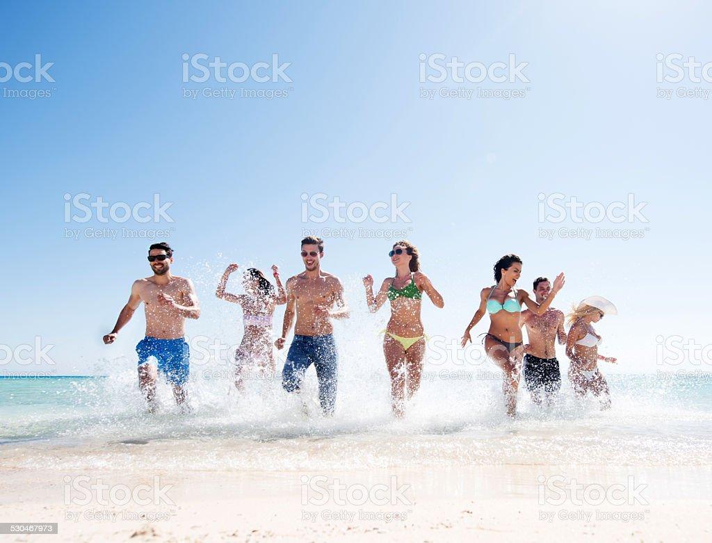 Happy people having fun in the sea. stock photo