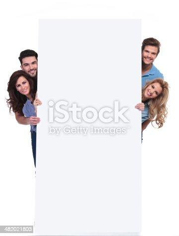 istock happy people hiding behing a big blank billboard 482021803