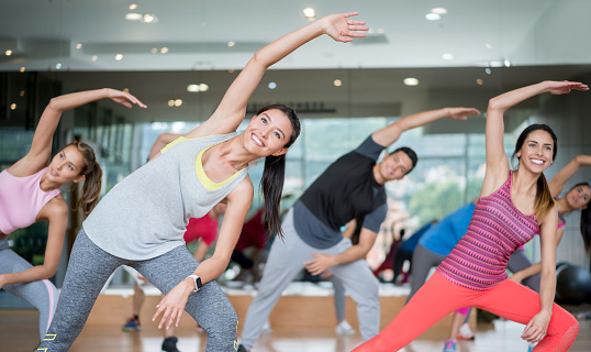 Group of people in an aerobics class at the gym stretching looking very happy – fitness concepts