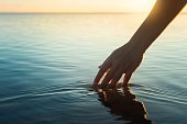 istock Happy people in nature. A woman feeling and touching the ocean water during sunset. 1299887977