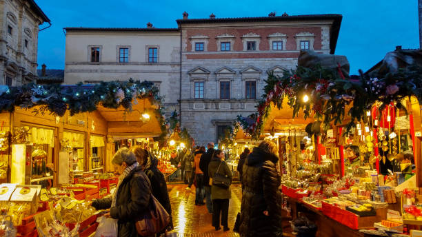 Happy people making shopping at the famous christmas market of Montepulciano in Tuscany, Italy Montepulciano, Italy - November 17, 2019: Montepulciano at Christmas is transformed into a Christmas market (free admission) with over sixty wooden houses where you'll find handicrafts, delicatessen products, decorations and gifts. Inside the Castle of Montepulciano, instead, children can enjoy the Christmas village set up just for them. In this photo there are many happy people making shopping at the christmas market in the main square of Montepulciano medieval town, Tuscany, Italy piazza grande stock pictures, royalty-free photos & images