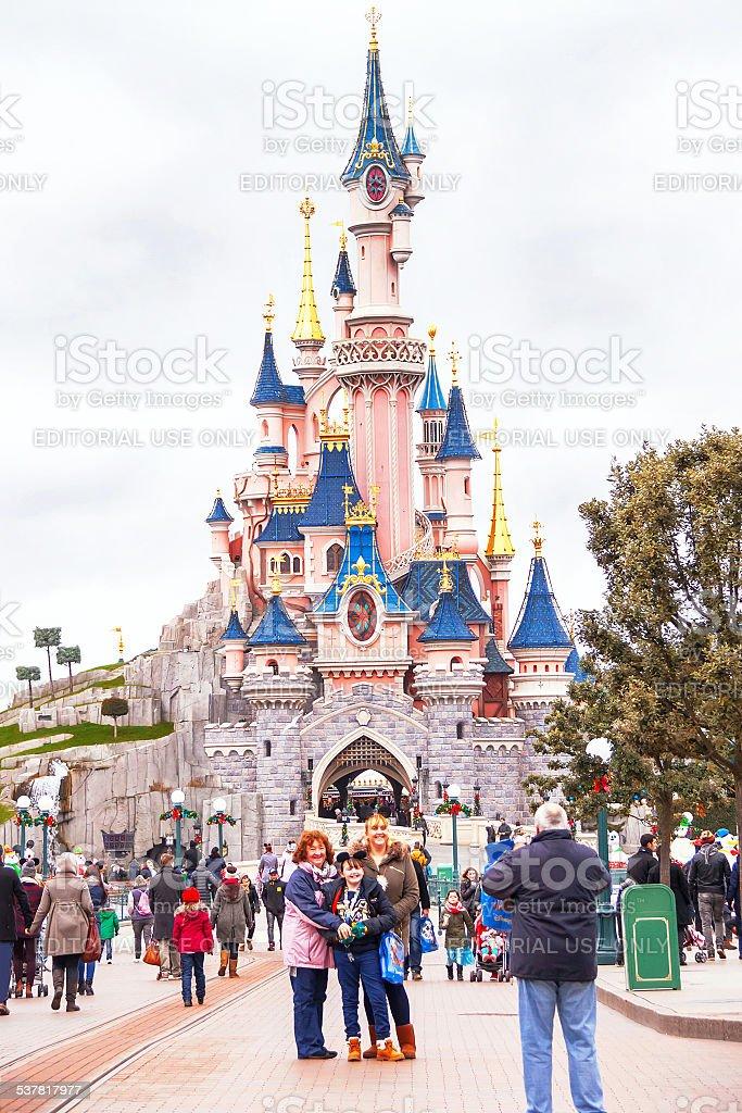 Happy people near castle in the Disneyland Paris. stock photo