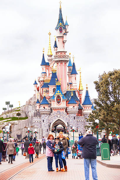 happy people near castle in the disneyland paris. - castle stock photos and pictures