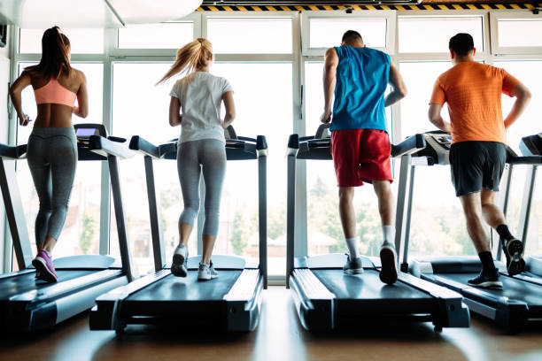 Happy people on treadmills in the gym Happy young people on treadmills in the gym treadmill stock pictures, royalty-free photos & images