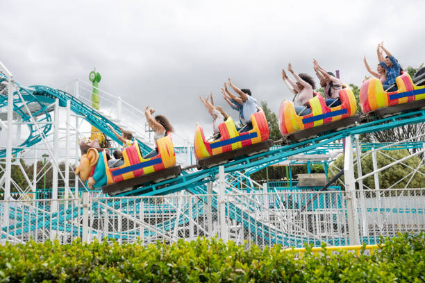 Happy people riding on a rollercoaster at an amusement park Happy group of people having fun riding on a rollercoaster in an amusement park - lifestyle concepts amusement park stock pictures, royalty-free photos & images