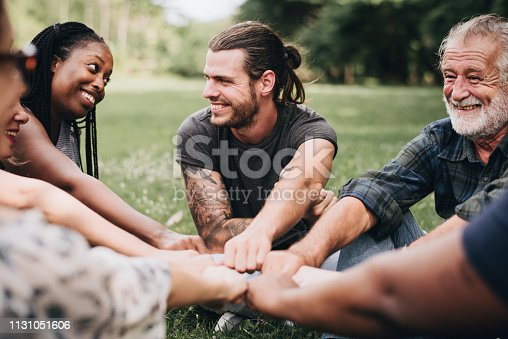 1094812112 istock photo Happy people stacking hands together in the park 1131051606