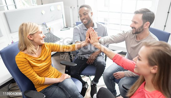 istock Happy people team giving high five in office. 1159040696