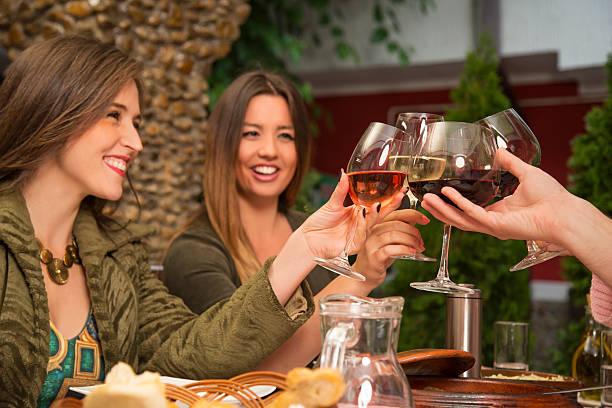 Glückliche Menschen Anstoßen mit Wein beim Mittagessen. – Foto