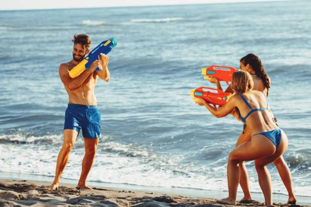 Glückliche Menschen mit Wasserpistolen viel Spaß am Strand am Meer – Foto