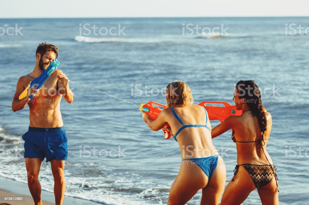 Happy people with water guns have fun on the beach by the sea stock photo