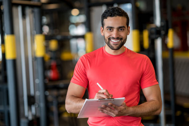 Happy personal trainer working at the gym stock photo