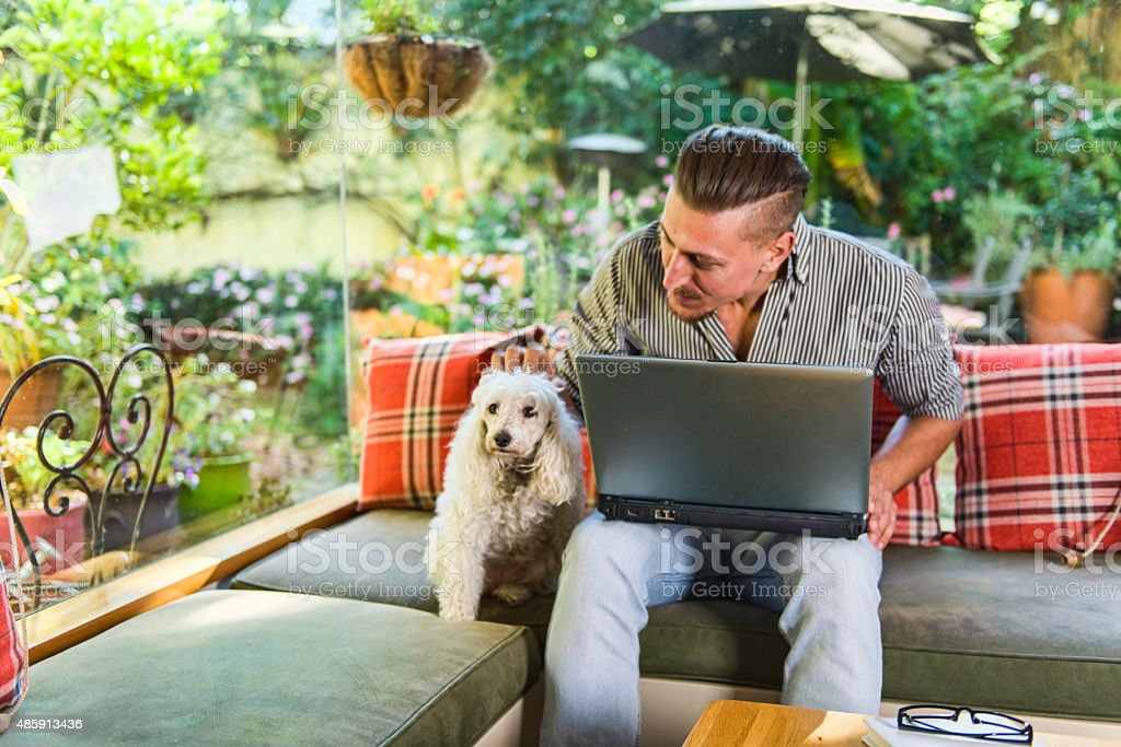 An image of a Caucasian guy with his dog