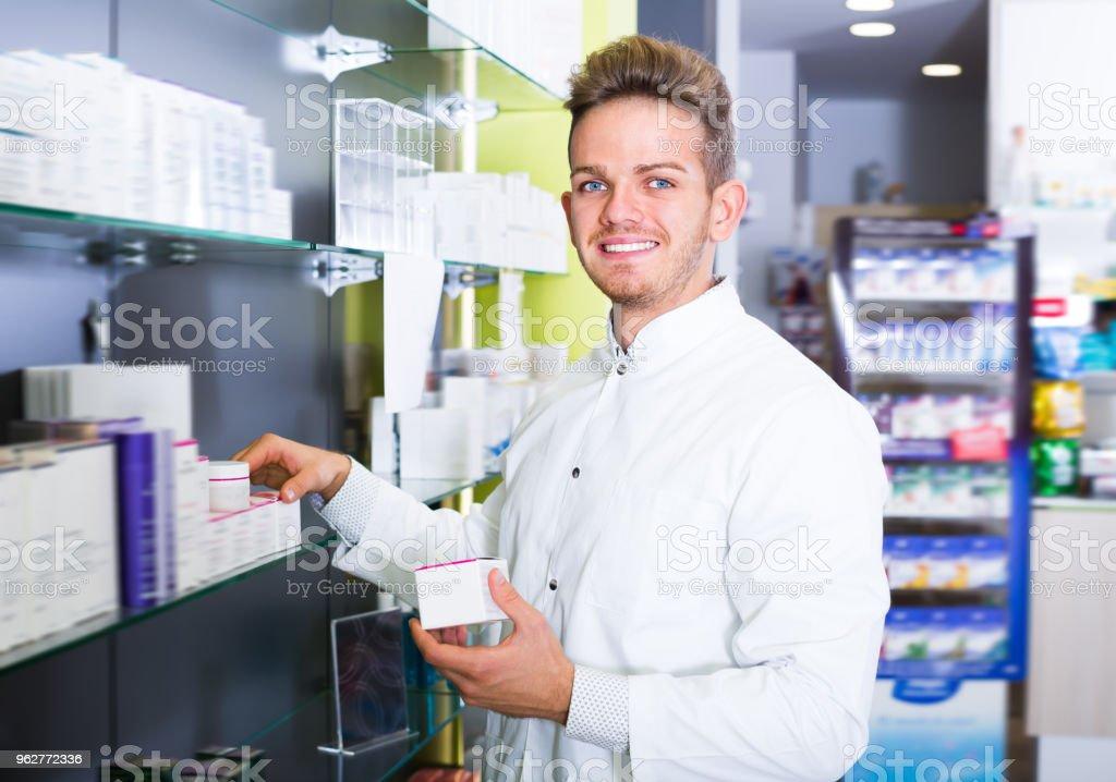 Happy pharmacist standing among shelves - Foto stock royalty-free di Adulto