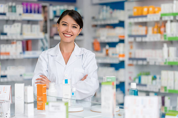 Happy pharmacist working at a drugstore stock photo