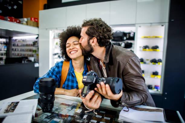 Glücklicher Fotograf küsst seinen Partner auf der Wange, während er eine DSLR-Kamera in einem Fotomate-Geschäft hält – Foto