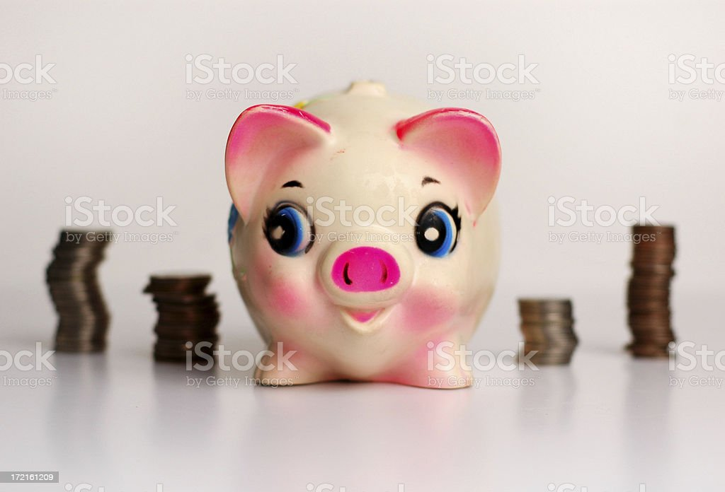 Happy Piggy Bank Standing with Stacks of Coins royalty-free stock photo
