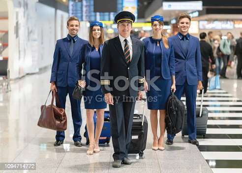 Portrait of a happy pilot with his cabin crew at the airport and looking at the camera smiling - traveling concepts
