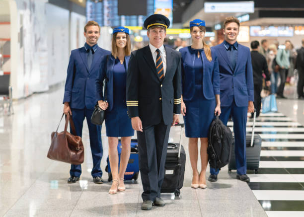 Happy pilot with his cabin crew at the airport Portrait of a happy pilot with his cabin crew at the airport and looking at the camera smiling - traveling concepts cabin crew stock pictures, royalty-free photos & images