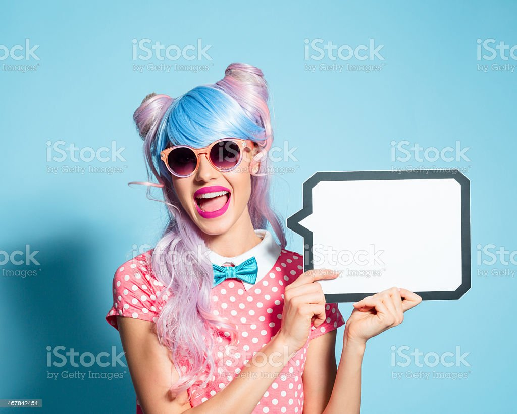 Happy pink hair manga style girl holding speech bubble Portrait of excited manga style blue-pink hair girl wearing sunglasses and pink polka dot dress with collar and bow tie. Standing against blue background, holding a speech bubble in hand and laughing at camera. Studio shot, one person. 2015 Stock Photo