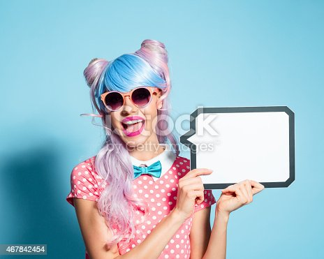 Portrait of excited manga style blue-pink hair girl wearing sunglasses and pink polka dot dress with collar and bow tie. Standing against blue background, holding a speech bubble in hand and laughing at camera. Studio shot, one person.