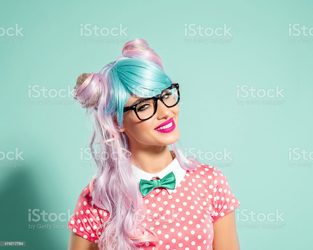 Happy pink-blue hair manga style girl wearing nerd glasses Portrait of manga style blue-pink hair girl wearing nerd glasses and pink polka dot dress with collar and bow tie. Standing against turquoise background and smiling at camera. Studio shot, one person. 2015 Stock Photo