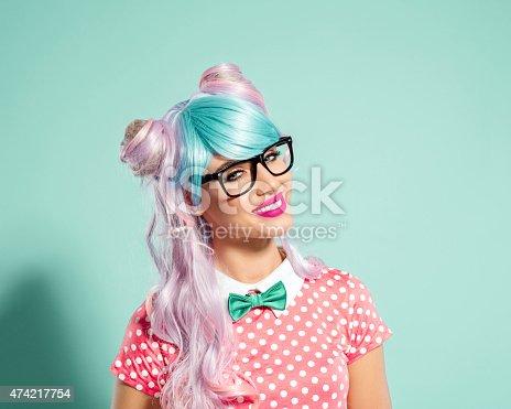 istock Happy pink-blue hair manga style girl wearing nerd glasses 474217754