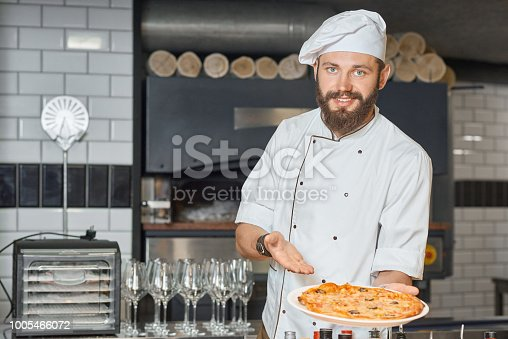 istock Happy pizzaiolo demonstrating fresh baked delicious pizza. 1005466072