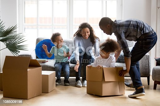 istock Happy playful African American family moving in new apartment 1085009198