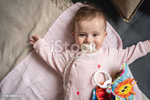 4 month old baby girl lying on bed