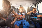 Three kids laughing in car on a road trip. Kids are aged 11 and 8. The kids are laughing and playing. Sunny summer day.\nNikon D810.